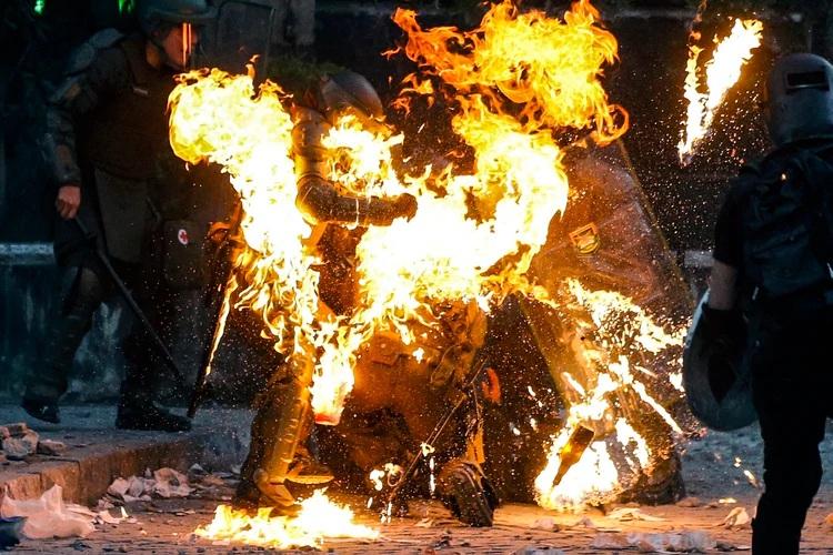 Los carabineros envueltos en llamas en Santiago (AFP)